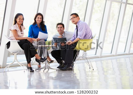 Businesspeople Having Meeting Around Table In Modern Office - stock photo