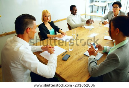 Businesspeople having meeting around table in office - stock photo