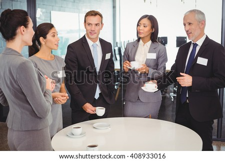 Businesspeople having tea and interacting during breaktime in office - stock photo
