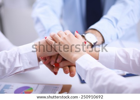 Businesspeople holding hands united over meeting table - stock photo