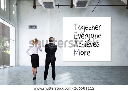 "businesspeople in a rendered industrial room with a canvas and the crossword ""TEAM - together everyone achieves more"" - stock photo"