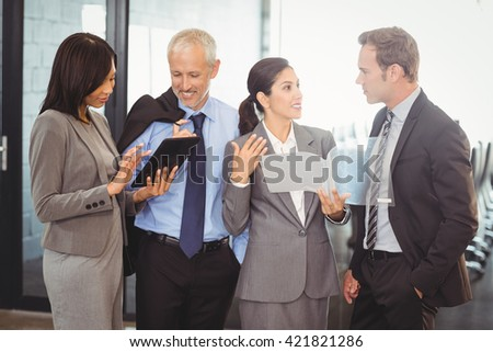 Businesspeople interacting and working in office - stock photo