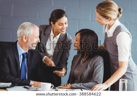 Businesspeople interacting in conference room in office - stock photo