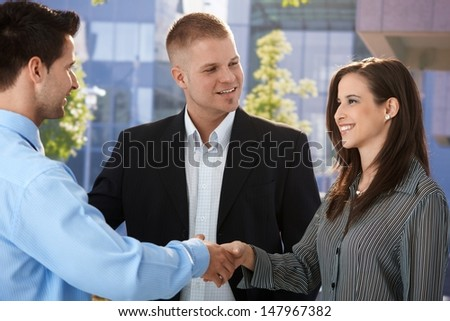 Businesspeople introducing outside of office, shaking hand, smiling. - stock photo