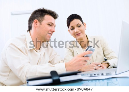 Businesspeople looking at cellphone screen, smiling. - stock photo
