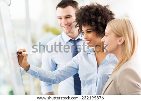 Businesspeople looking at flipchart in office  - stock photo