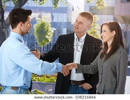 Businesspeople meeting outside of office, businessman introducing female colleague, smiling. - stock photo