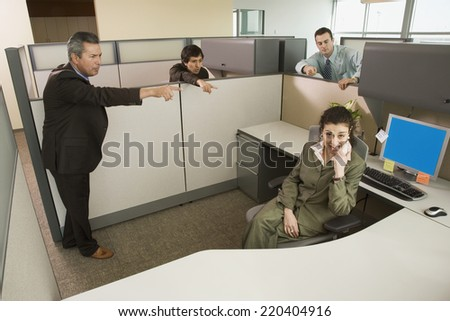 Businesspeople pointing at co-worker in office cubicle - stock photo