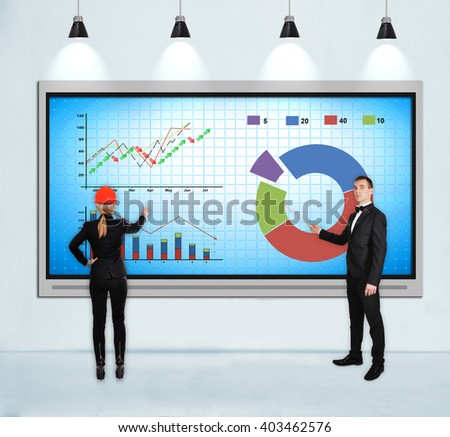 businesspeople pointing to tv screen with stock chart - stock photo