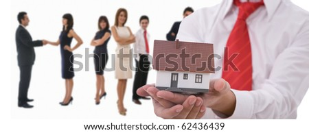 Businesspeople shaking hands and posing with dummy of house - stock photo