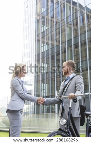 Businesspeople shaking hands outside office building