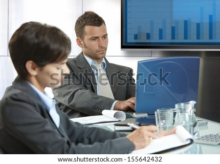 Businesspeople sitting around table at meetingroom, working. - stock photo