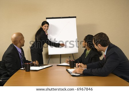 Businesspeople sitting at conference table smiling while businesswoman gives presentation.