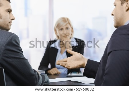 Businesspeople sitting at table in office, discussing work at meeting. Focus on explaining hand.? - stock photo