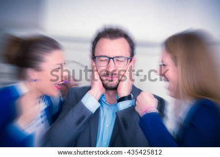 Businesspeople sitting at the office desk. Annoyed businessman covering his ears with hands and two women yelling at him from his left and right side.      - stock photo