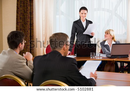 Businesspeople sitting at the table listening to their colleague's speech in conference room - stock photo