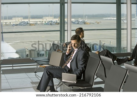 Businesspeople sitting in the airport. - stock photo