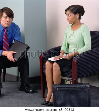 Businesspeople sitting in waiting room - stock photo