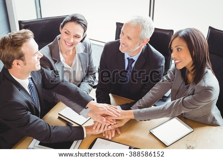 Businesspeople stacking hands in conference room in office - stock photo