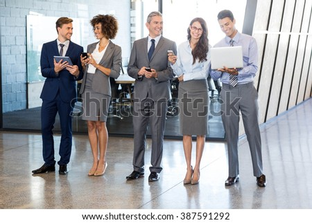 Businesspeople standing in a row and using mobile phone, lap top and digital tablet in office - stock photo