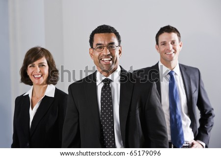 Businesspeople standing in office, focus on African American businessman, 40s - stock photo
