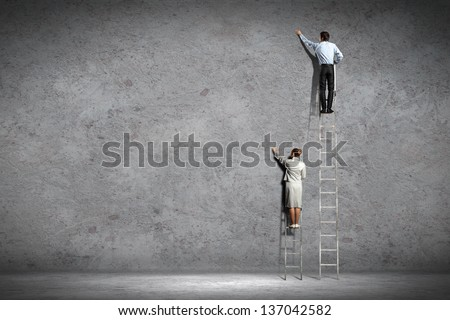 businesspeople standing on ladder drawing diagrams and graphs on wall - stock photo