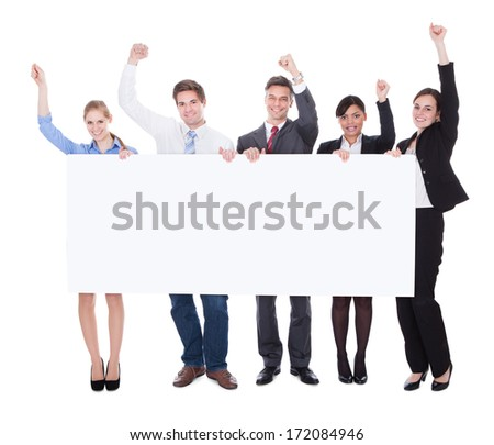 Businesspeople Standing With Billboard Raising Hand Over White Background - stock photo