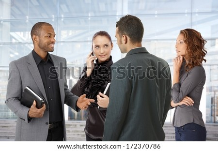 Businesspeople talking front of office building. - stock photo