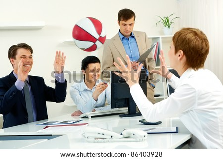 Businesspeople throwing basketball in the office - stock photo