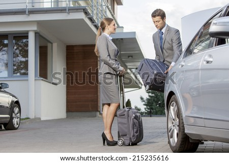 Businesspeople unloading luggage from car outside hotel - stock photo