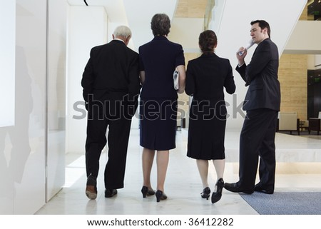 Businesspeople walking in a corridor to a meeting. - stock photo