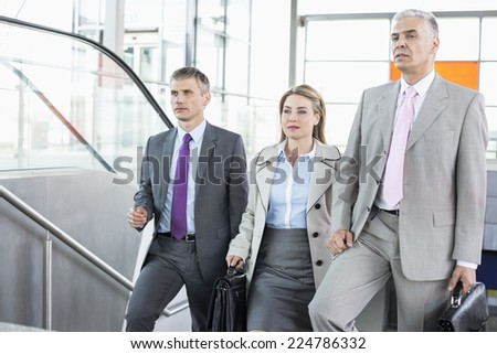 Businesspeople walking up stairs in train station - stock photo