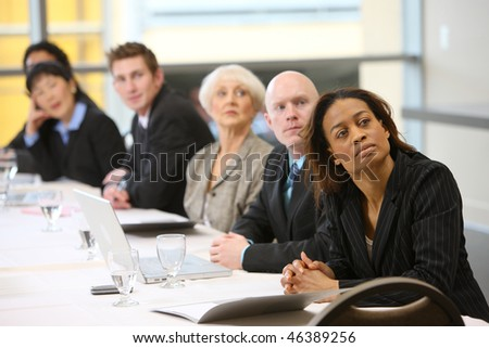Businesspeople watch presentation in board room - stock photo