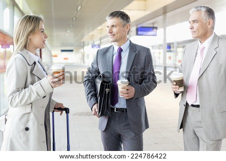 Businesspeople with coffee cups talking at railroad platform - stock photo