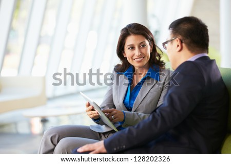Businesspeople With Digital Tablet Sitting In Modern Office - stock photo