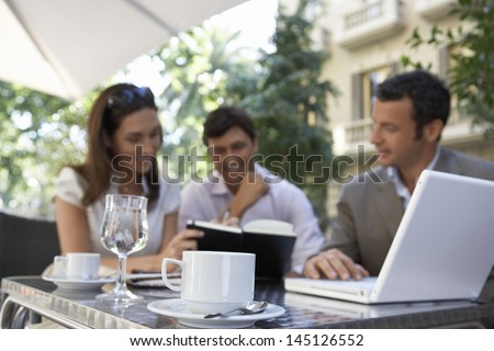 Businesspeople with laptop and diary having a meeting at outdoor cafe - stock photo