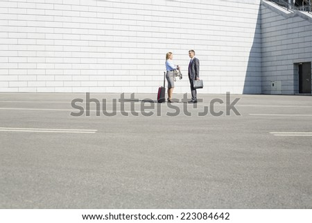 Businesspeople with luggage talking on street - stock photo