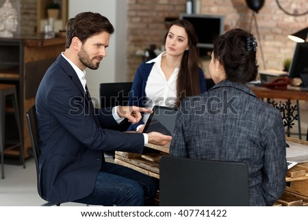 Businesspeople working in office, talking, using tablet computer. - stock photo