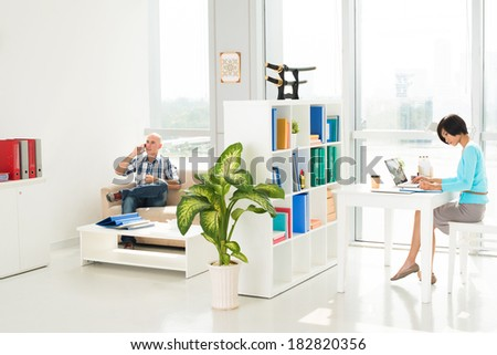Businesspeople working in their own part of office, woman networking while man talking by phone  - stock photo