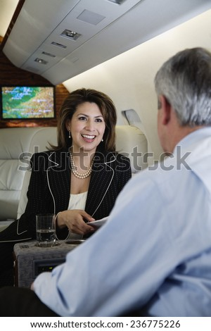 Businesspeople Working on Private Jet - stock photo