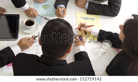 Businesspeople working together at meeting, discussing document - stock photo