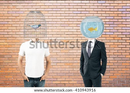 Businessperson and casually dressed man with fishtank and birdcage instead of heads on brick background - stock photo