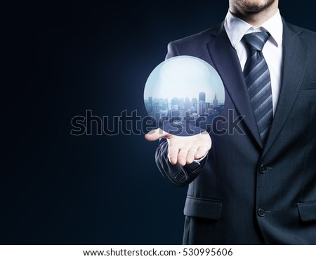 Businessperson holding abstract sphere with city on dark background