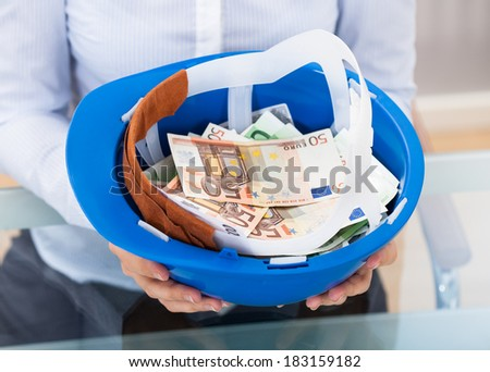 Businessperson Holding Blue Hardhat Full Of Euro Banknotes - stock photo