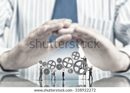 Businessperson holding gears and cogwheels mechanism in hands - stock photo