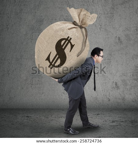 Businessperson in formal suit carrying money bag with dollar currency symbol