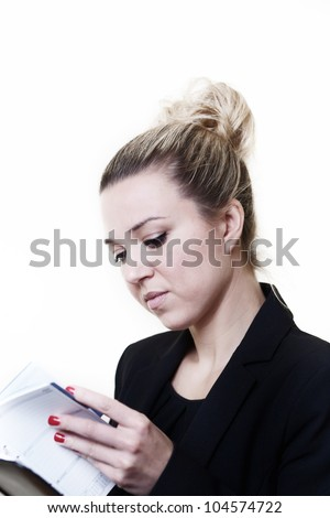 businessperson looking in her filofax making sure she can keep to her engagements - stock photo
