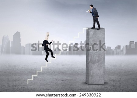 Businessperson runs on the stairs to meet his leader, called with a megaphone from the top - stock photo