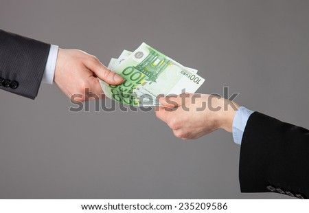 Businessperson's hand accepting an offer of money on grey background
