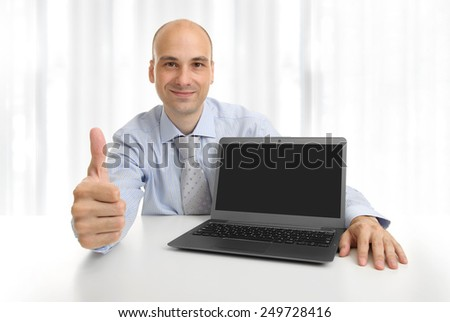 Businessperson showing a laptop with blank screen for copy space - stock photo